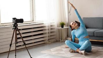 Mujer bloguera en ropa deportiva graba video en cámara en casa foto