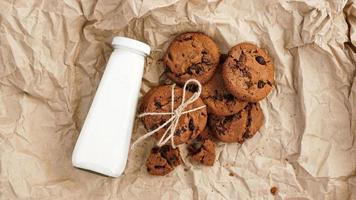 Cookies with chocolate drops on craft paper and bottle of milk photo