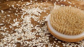 Wooden round massage brush on a wooden background. Scattered oatmeal. photo