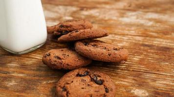 Chocolate cookie with milk on wooden table. Homemade cookies. photo