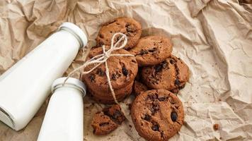 Cookies with chocolate drops on craft paper and bottles of milk photo