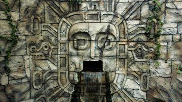 Stone wall in the jungle. Head mask and waterfall from the mouth photo