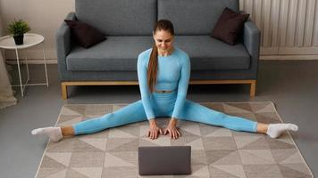 A beautiful woman in a blue tracksuit is stretching photo