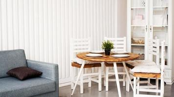 Round wooden dining table and white chairs photo