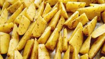 Sliced raw potatoes on a baking sheet with spices photo