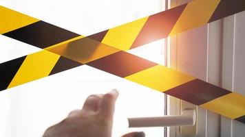 cinta amarilla coronavirus quédate en casa. una mano alcanza la manija de la puerta foto