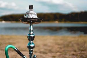 Hookah bowl stands in nature by the river close up photo
