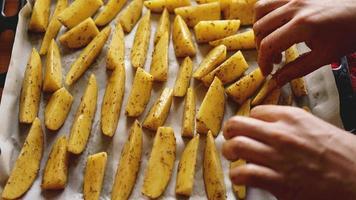 manos - patatas crudas en rodajas en una bandeja para hornear foto