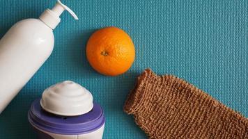 loción, naranja, esponja de ducha y masajeador anticelulítico foto
