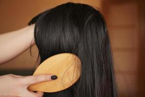 Female hand holds a black wig with long hair and combs a wooden comb photo