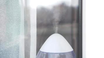 El humidificador ultrasónico blanco en una ventana de la sala de estar foto