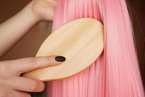 Female hand holds a pink wig with long hair and combs a wooden comb photo