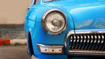 Blue retro car. Old vintage car. Headlight close up photo