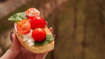 mano de mujer con bruschetta de tomate cherry. aperitivo de vino italiano foto