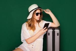 Beautiful girl sits near a suitcase photo