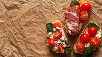 tres bruschetta fresca sobre papel artesanal. delicioso refrigerio foto