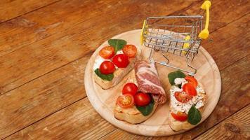 bruschetta italiana sobre una tabla de madera. cesta de la compra foto