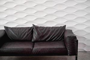 Sofá de cuero negro sobre fondo blanco en estudio foto