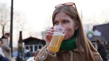 mujer joven bebe cerveza ligera. comida callejera y patio de comidas. foto