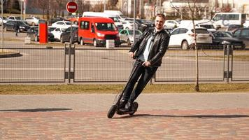 Hombre moderno montando scooter eléctrico en la ciudad foto