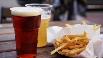 Dark and light beer and fries on a wooden table photo