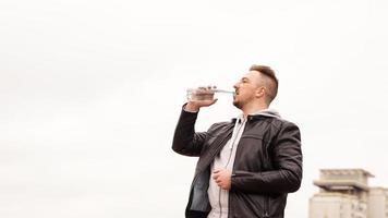 Un hombre con una chaqueta de cuero bebe agua de una botella contra el cielo foto