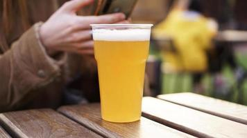 cerveza light en un vaso de plástico. niña bebiendo cerveza en el patio de comidas foto