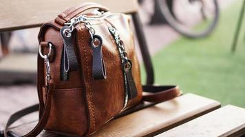 Brown leather bag outside. Blurred summer background photo