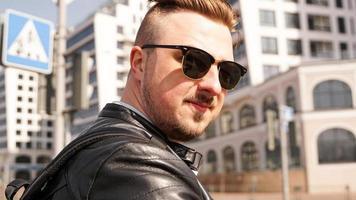 un atractivo hombre vestido con chaqueta de cuero negro con gafas de sol oscuras foto