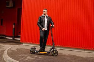 Young attractive man on electric scooter over red background photo