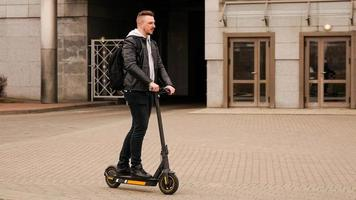 Tall man on an electric scooter against photo