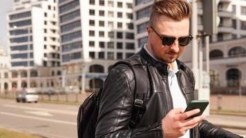 A young man in sunglasses looks at the phone photo