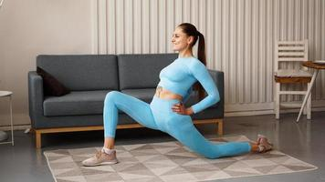Fit woman doing front forward one leg step lunge exercises workout photo