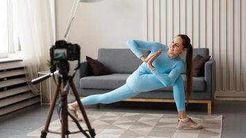 Woman blogger in sportswear shoots video on camera at home photo