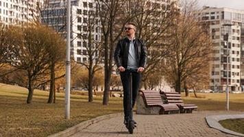 Joven con una chaqueta negra y gafas de sol monta un scooter electrónico foto