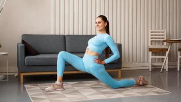 Colocar mujer haciendo ejercicios de estocada de paso de una pierna hacia adelante foto