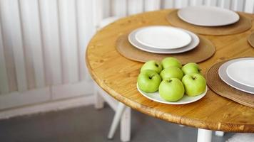 Green apples on a white plate on a wooden table photo