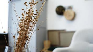 A vase with dry flowers on a table. Scandinavian photo