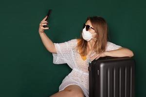 Beautiful girl with Medical mask on the face taking selfie photo