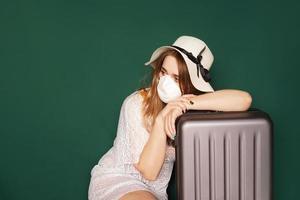 El viajero con una máscara médica en la cara está esperando. foto