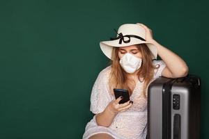Turista de niña en una máscara médica se sienta con equipaje sobre un fondo verde foto