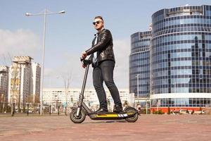Modern man riding electric scooter in the city photo