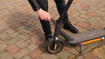 Young man folding an electric scooter in street outdoor. photo