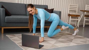 Hermosa joven haciendo ejercicio físico en casa con su computadora portátil foto
