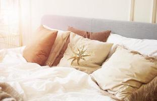 Closeup pillow on bed in warm bedroom modern interior photo