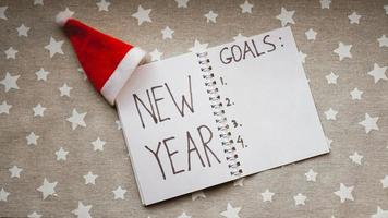 Notebook is with New year goals text photo