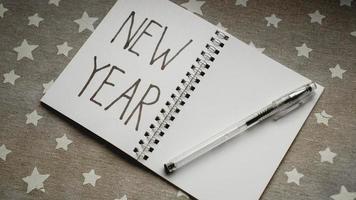 Cuaderno con bolígrafo para escribir metas de año nuevo. foto