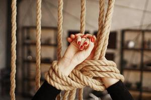 Tied with a rope female hands with red nails photo