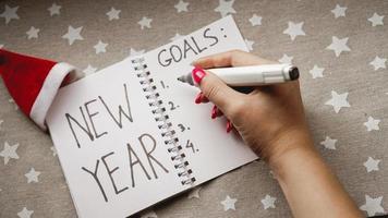 El cuaderno es con el texto de las metas de año nuevo con la mano. foto