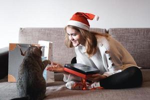 Happy girl in santa hat opening christmas gift box photo
